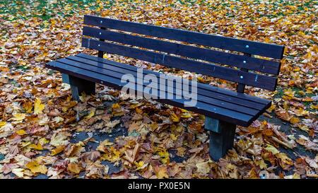 Holzbank und bunte Blätter im Herbst in einem mehrstöckigen Haus Innenhof. - Stockfoto