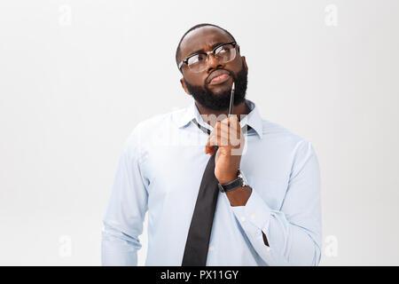 Porträt einer nachdenklich Afrikanische amerikanische Geschäftsmann in einem grauen Anzug denken mit Stift auf der Hand. - Stockfoto