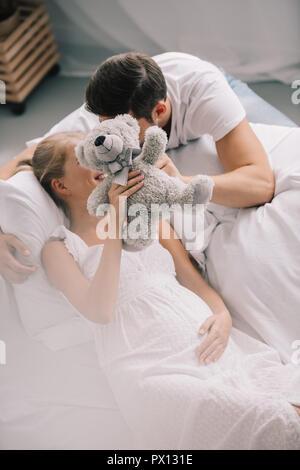 Verdeckt Sicht des Menschen und schwangere Frau in weißen Nachthemd holding Teddybär auf dem Sofa zu Hause - Stockfoto