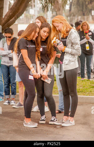 Ein jugendlich Mädchen Verzögerungen eine Banane essen, ihre Freunde in einem Gebet vor einem Festival in Costa Mesa, CA. - Stockfoto