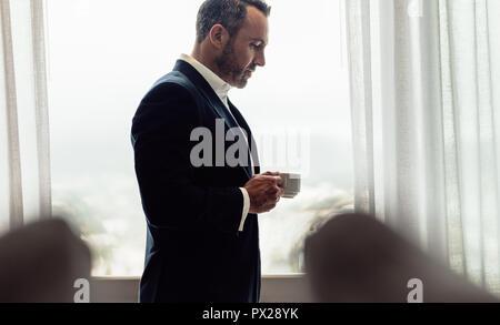 Unternehmer stehen im Hotel Zimmer mit einer Tasse Kaffee. Reifer Mann im Anzug trinken Kaffee im Hotel Zimmer am Morgen. - Stockfoto