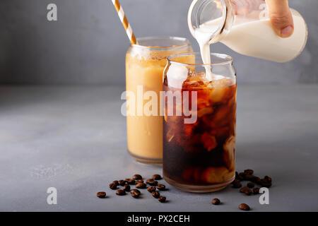 Kalte Gebräu Eiskaffee in ein Glas mit Milch oder Kaffeesahne in Gießen - Stockfoto