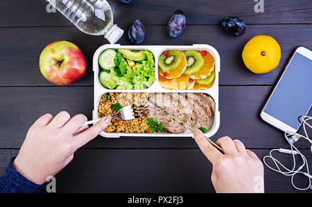 Ansicht von oben mit den Händen essen gesund essen mit Bulgur, Fleisch und frisches Gemüse und Obst auf einem Holztisch. Fitness und gesunde Lebensweise. - Stockfoto