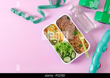 Gesundes Mittagessen mit Bulgur, Fleisch und frisches Gemüse und Obst auf einem rosa Hintergrund. Fitness und gesunde Lebensweise. Brotdose. Ansicht von oben - Stockfoto