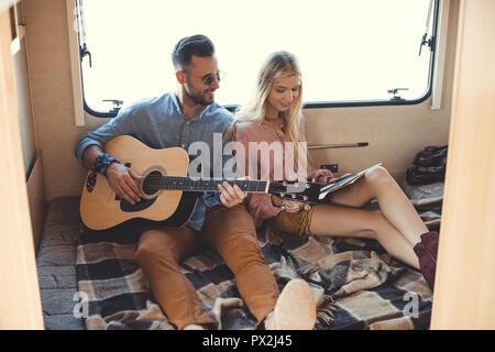 Glücklich Freund spielen an der Gitarre während Freundin holding Schallplatte innen Wohnmobil - Stockfoto
