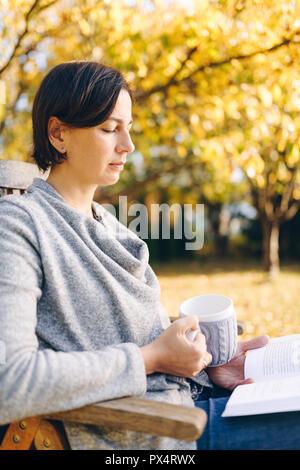 Frau mit warmem Strick Kleidung trinken eine Tasse heißen Tee oder Kaffee und ein Buch lesen, im Freien in der Sonne - Jahreszeit, Literatur, Freizeit und pe - Stockfoto