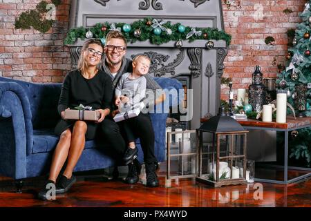 Glückliche Familie Spaß zu Hause haben. Im Zimmer unter dem Dach mit Ziegeln. Junge Eltern mit kleinen Sohn. Vater, Mutter und ihr Baby. Frohes neues Jahr. Geschmückter Weihnachtsbaum - Stockfoto