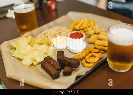 Lagerbier und Snacks auf Holztisch. Nüsse, Chips, Erdnüsse, Toast, Cracker. Vorspeise fast food. Handwerk Bier. Beerboard. Tomaten, Käse und Knoblauch sauc - Stockfoto
