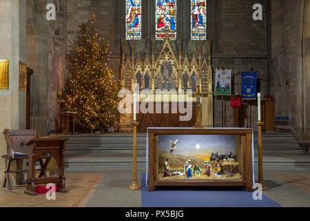 Innenansicht der Krippe, mit einem Krippenspiel, Weihnachtsbaum und Altar in der Pfarrkirche in Boston Spa in West Yorkshire - Stockfoto