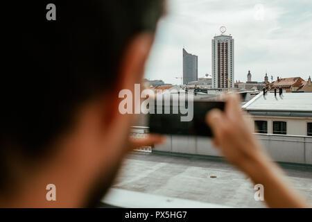 Nahaufnahme von Rückansicht der junge Mann Fotografieren einer Skyline der Stadt mit seinem Smartphone - Stockfoto