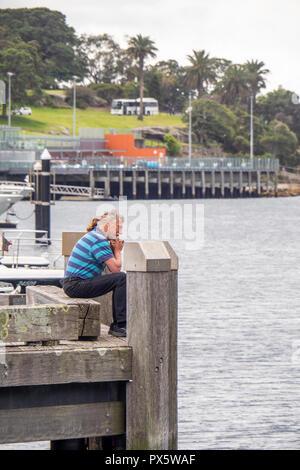 Miuddle alter Kaukasischer Mann am Ende einer Anlegestelle Woolloomooloo Bay Sydney NSW Australien sitzen. - Stockfoto