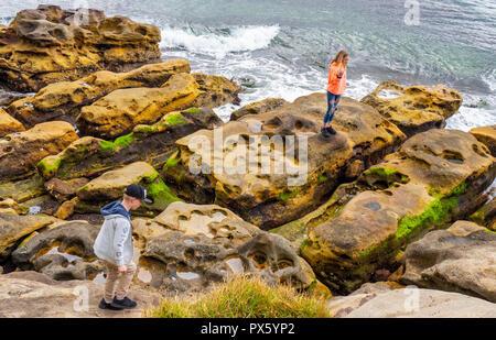 Teenager Jungen und Mädchen klettern auf sandsteinfelsen an Mrs Macquaries Point im Hafen von Sydney Sydney, NSW, Australien. - Stockfoto