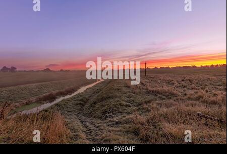 Dämmerung bricht über die Felder, die mit einem Stream durch läuft. Ein roter Himmel ist Overhead. - Stockfoto