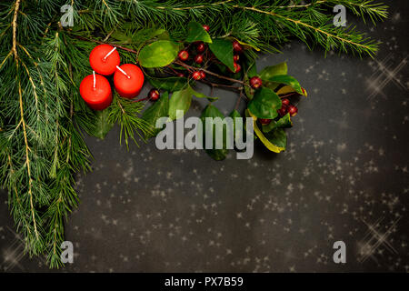 Weihnachtsschmuck mit kleinen roten Beeren, helle Kugeln, rote Kerzen und eine Niederlassung auf eine Schwarze Schiefertafel mit einem Bereich zum Hinzufügen von Text - Stockfoto