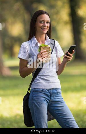 Schöne Geschäftsfrau ruht sich aus Arbeit, essen Sandwich und über Telefon. - Stockfoto