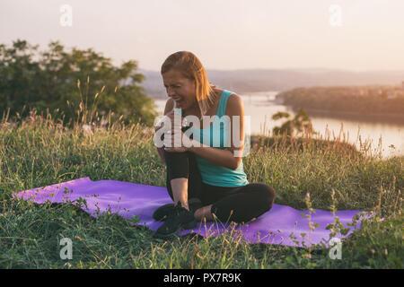 Sportliche Frau, sport Verletzung, während auf der Trainingsmatte mit einem Stadtbild und Fluss behinde ihr sitzen. - Stockfoto