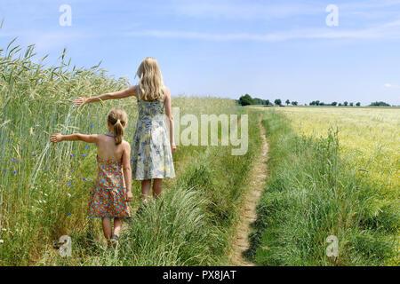 Junge Frau mit einem kleinen Mädchen zu Fuß auf der grünen Wiese, blauen Himmel im Hintergrund - Stockfoto