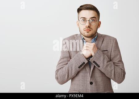 Taille- schuss besorgt, intensive Süße europäischen Mann mit Borsten und coolen Haarschnitt in formalen Jacke ballte die Hände in der Nähe der Brust Sorge und Mühe in die Kamera starrt, als ob Anhörung schockierende Offenbarung - Stockfoto