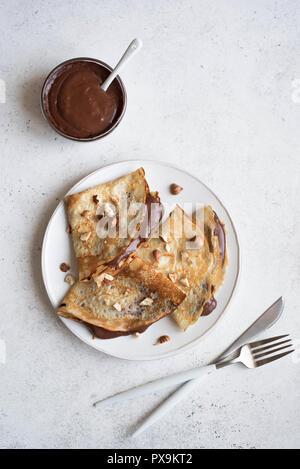 Pfannkuchen mit Schokolade und Haselnüssen. Hausgemachte dünne Crepes für Frühstück oder Dessert auf weissem, kopieren. - Stockfoto