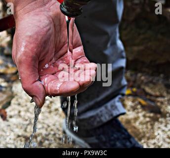 Strom der sauberes Wasser in des Menschen Hand/Hände gießen Fang sauber fallenden Wassers hautnah. Umweltkonzept. - Stockfoto