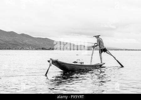 Reisen lokale junge burmesen männliche Fischer tragen geprüft, t-shirt, mit Stick und net zu fischen, Balancieren auf einem Fuß auf dem Boot, Inle Lake Myanmar, Birma - Stockfoto