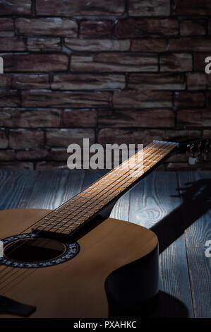 Ein Lichtstrahl beleuchtet eine Gitarre im Dunkeln liegen. - Stockfoto