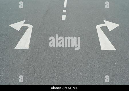 Pfeile nach rechts und nach links auf eine asphaltierte Straße - ein Konzept für Entscheidungen - Durch Drehen nach Links oder Rechts