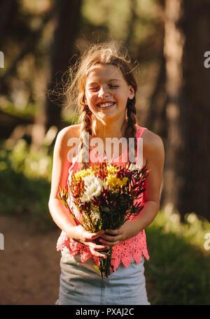 Glückliches Mädchen mit einem Blumenstrauß in der Hand. Stehendes Mädchen im Freien mit einem Blumenstrauß in der Hand. - Stockfoto