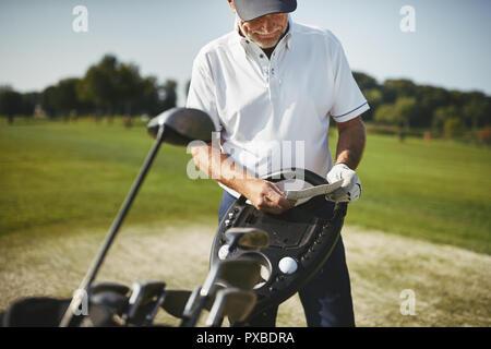 Sportliche älterer Mann, der durch seine Vereine und Lesen sein Scorecard während einer Runde Golf genießen Sie an einem sonnigen Tag - Stockfoto