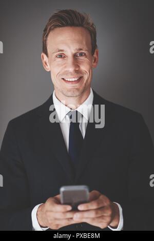 Selbstbewussten jungen Geschäftsmann in Anzug und lesen eine SMS auf sein Handy während vor grauem Hintergrund stehend - Stockfoto