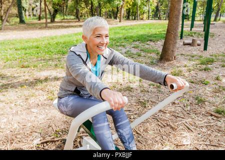 Ältere Frau im Sport Kleidung Ausübung der Outdoor Fitness Park mit Rudergerät, gesunden Lebensstil älterer Menschen.