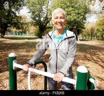 Ältere Frau im Sport Kleidung Ausübung der Outdoor Fitness Park, gesunden Lebensstil reifen Menschen.