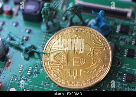 Bitcoin unter Angriff vier Miniatur Männer umgeben von Haufen bitcoin. Miniatur Figur Spielzeug in der Nähe von bitcoin - Stockfoto