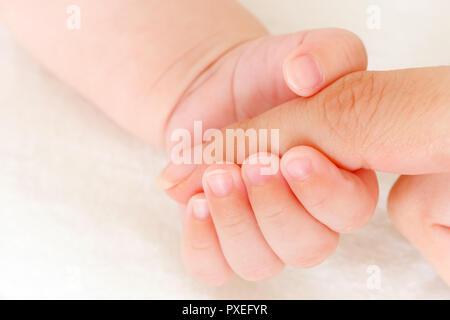 Nahaufnahme von Babys Hand hielt Mutters finger - Stockfoto