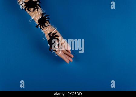 Weibliche Hand in Weiß mit schwarzem Papier Spinnen auf blauem Hintergrund gewickelt. Halloween Konzept. Papier schneiden Stil. Ansicht von oben - Stockfoto