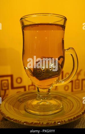 Heißen Kamillentee in transparenten Tee Tasse mit niedlichen Tea Leaf Filter vor der gelben wand serviert. - Stockfoto