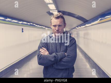 Portrait des jungen Mannes Gefühl verzweifelt und einsam stehende in der Nähe der U-Bahn weg trägt eine Kapuze Denken in Stress und deprimiert. - Stockfoto