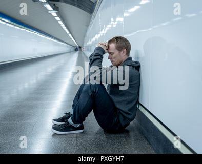 Miserable arbeitslose junge Mann weinen Drogensüchtigen Obdachlosen in Depression stress sitzen auf dem Boden Street U-Bahn Tunnel suchen verzweifelt lehnte sich an der Wand - Stockfoto