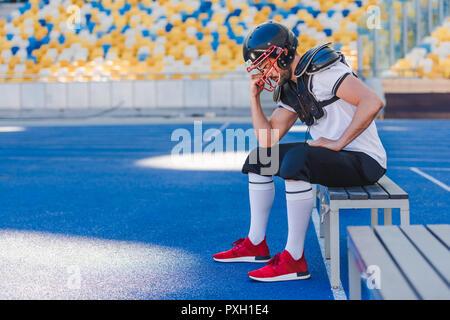 Seitenansicht der jungen amerikanischen Fußball Spieler, der Käfig der Helm beim Sitzen im Stadion - Stockfoto