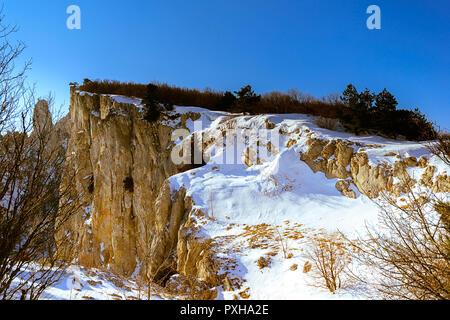 Berg, teilweise mit unberührten Schnee bedeckt, wilde Natur von Russland, auf Bäume, Pinien, auf der linken ein Fragment der Zweige - Stockfoto