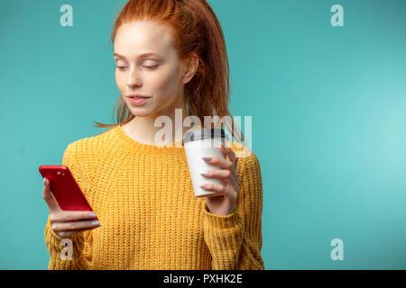 Junge rothaarige Frau mit Kaffee und Smartphone über blauen Hintergrund isoliert - Stockfoto