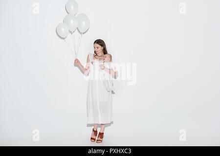 Die ganze Länge der jungen Mutter in stilvollem Weiß Kleid tragen adorable Baby Tochter und Holding Bündel Luftballons auf Grau - Stockfoto