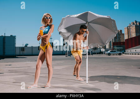 Junges attraktives Paar mit Sonnenschirm in Badebekleidung Gerben auf Parkplatz - Stockfoto