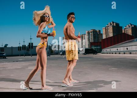 Junge glückliches Paar in Badebekleidung mit erfrischenden Cocktails stehen auf Parkplatz - Stockfoto