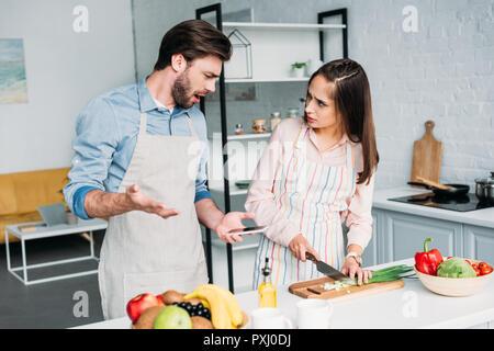 Gereizte Freund gestikuliert während Freundin Schneiden von Gemüse in der Küche - Stockfoto