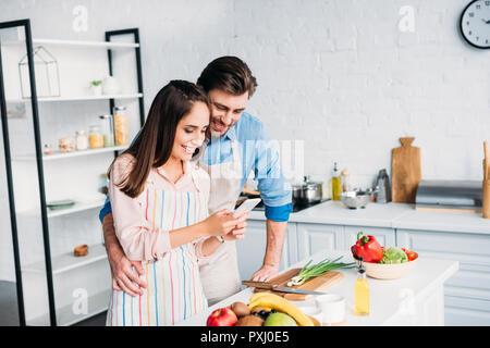 Paar umarmen und auf Smartphone beim Kochen in der Küche - Stockfoto