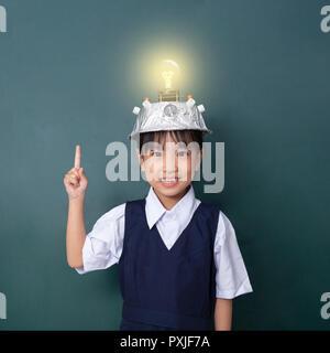 Asiatische chinesische Mädchen tragen Virtuelle Realität Helm und Zeigefinger bis zu Glühbirne gegen grüne Tafel - Stockfoto