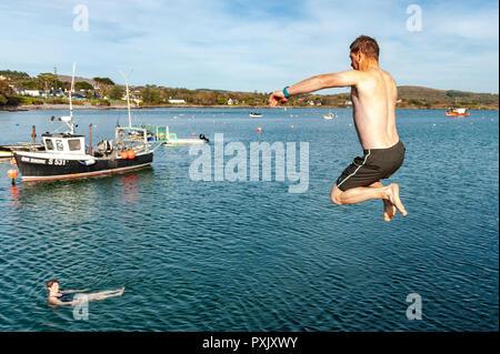 Schull, West Cork, Irland. 23 Okt, 2018. Clinton Copithorne von Ballydehob macht die meisten der ungewöhnlich warmen Wetter durch einen Sprung ins Meer aus Schull Pier. Sunshine hat die Reihenfolge der Tag heute mit Höhen von 13-15° Celsius in West Cork. Credit: Andy Gibson/Alamy Leben Nachrichten. - Stockfoto