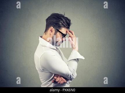 Seitenansicht des bärtigen Mann in Gläsern und weißes Hemd berühren Stirn in Depression und voller Gedanken - Stockfoto