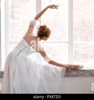 Junge Ballerina ist Stretching auf Dance Hall. - Stockfoto